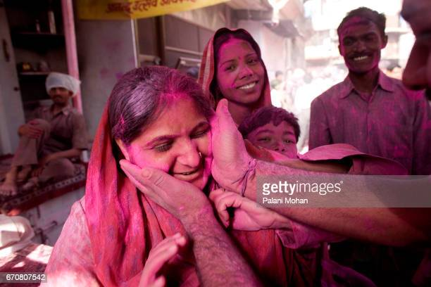 Indian women has red power placed on her face as part of Holi celebrations inside the side the Banke Bihari Temple to take part in the Holi...