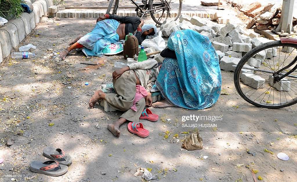 Indian women labourers nap on the roadside in the heat of New Delhi on June 5, 2013. The weather department has forecast India will receive normal rains this year, raising prospects of a stronger performance by Asia's third-largest economy.