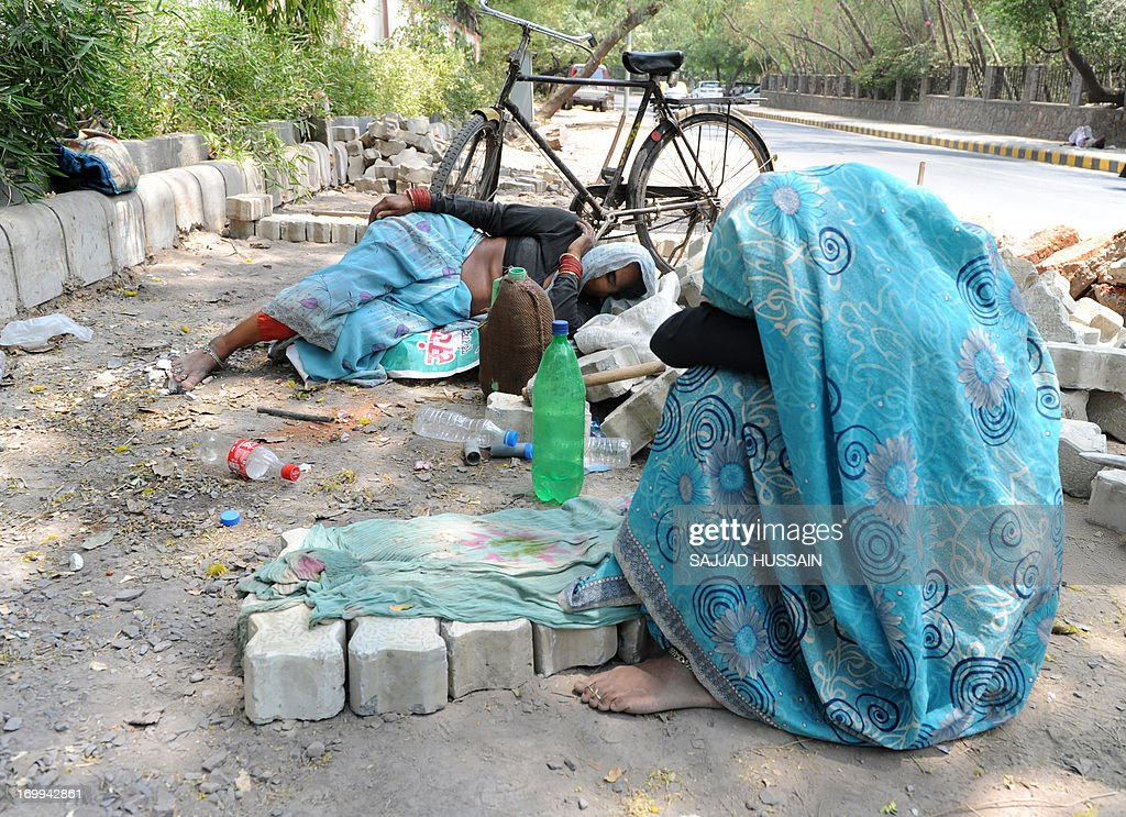 Indian women labourers take a nap on the roadside in the heat of New Delhi on June 5, 2013. The weather department has forecast India will receive normal rains this year, raising prospects of a stronger performance by Asia's third-largest economy.