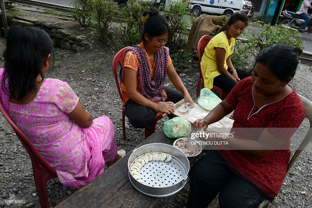 Indian women of a fast food shop prepare 'momos' to sell during a day long relaxation of an indefinite strike at Sukna village on the outskirts of Siliguri on August 31, 2013. Gorkha People's Liberation Front (GJM) called an indefinite strike throughout the month in Darjeeling and nearby hills. AFP PHOTO/ Diptendu DUTTA
