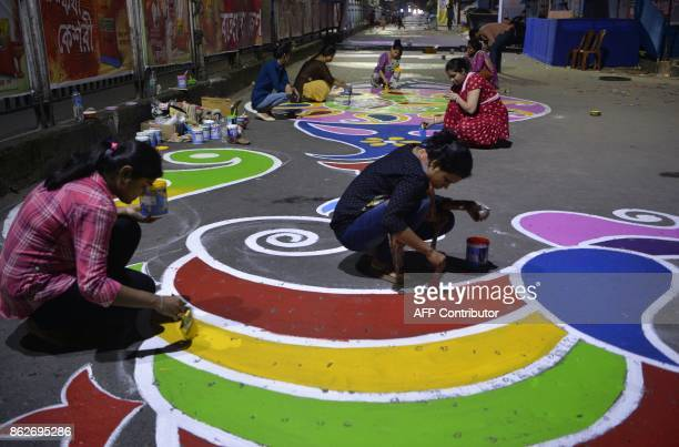 Indian women paint designs on the road during celebrations to mark Diwali in Siliguri early on October 18 2017 Diwali the Hindu festival of lights...