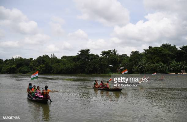 Indian women participate in a rowing competition as a part of Independence Day celebrations in Majhdia village of Nadia district east of Krishnanagar...