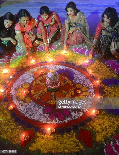 Indian women pose with earthen lamps ahead of Diwali the Hindu festival of lights in Siliguri on October 19 2014 Diwali the Festival of Lights marks...