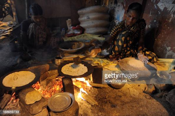 Indian women prepare Jowar roti a traditionally farmer's food on a road side in the outskirts of Hyderabad on May 13 2013 The Congress party which...