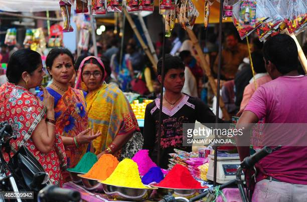 Indian women purchase colored powder for the 'holi' celebrations at a roadside stall in the old city of Allahabad on March 4 2015 'Holi' the festival...