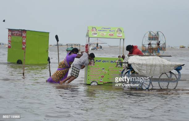 Indian women push a food cart stall in flood water at Marina Beach on the Bay of Bengal coast after heavy rain in Chennai on November 3 2017 The...