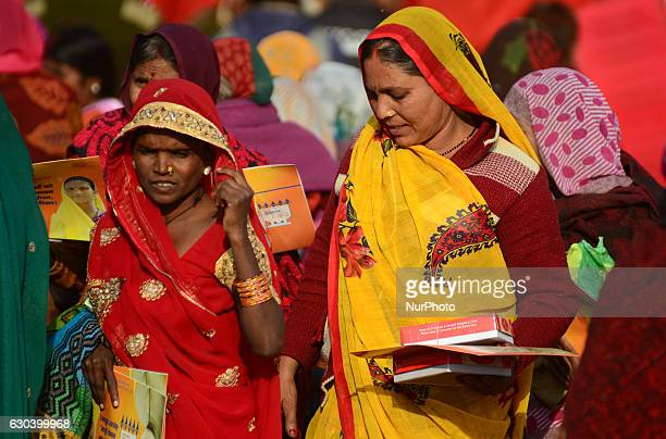 Indian women return after taking free gas connection card and lunch packets given by Minister of state for Patrolium and natural gas Mr Dharmendra...