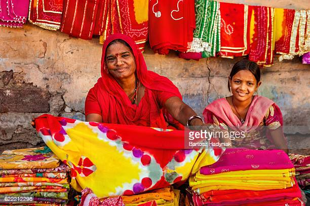 Indian women selling colorful fabrics