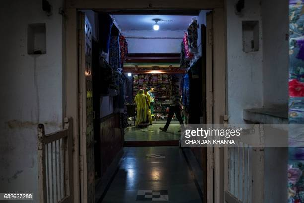 Indian women shop inside a commercial complex in Kekri some 78 kms south of Ajmer on May 13 in the northern state of Rajasthan / AFP PHOTO / CHANDAN...