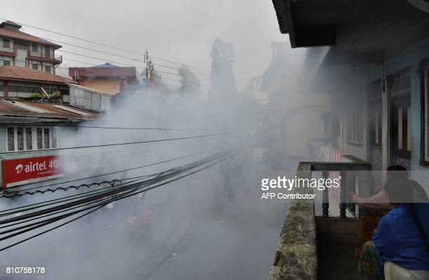 Indian women sit amidst tear gas fired by the police during clashes with Gorkhaland supporters during an indefinite strike called Gorkha Janamukti...
