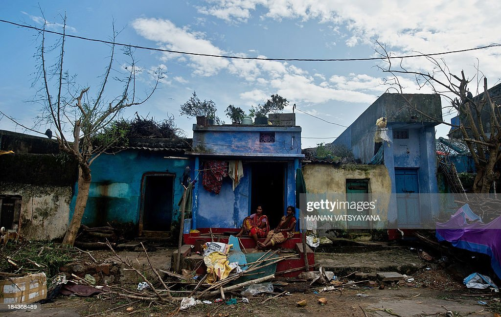 Indian women sit outside their house among cyclone debris at the fishermen's colony in Gopalpur on October 13, 2013. Cyclone Phailin left a trail of destruction along India's east coast and up to seven people dead after the biggest evacuation in the country's history helped minimise casualties.