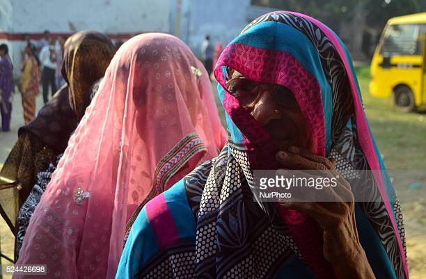 Indian women stand in a queue as they wait for their number to cast their vote for first phase of Panchayat elections at a polling centrein Rampur23...