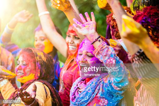 Indian women throwing colored Holi powder