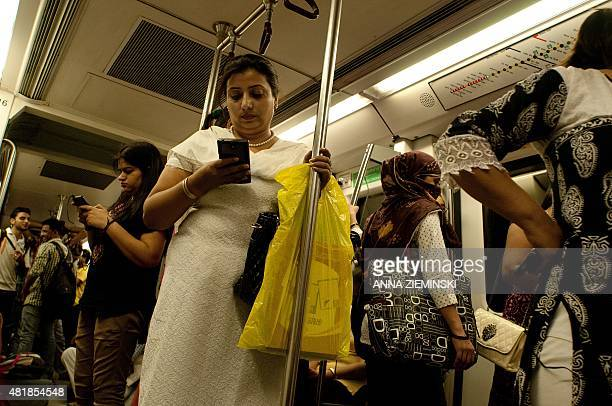Indian women use their smartphones as they travel in the carriage reserved for women on the metro in New Delhi on July 3 2015 AFP PHOTO/ Anna...
