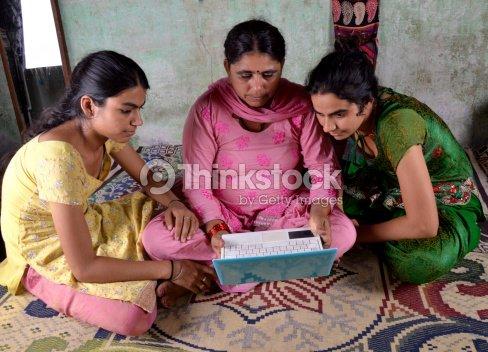 Indian mujeres usando ordenador portátil con sus hijas : Foto de stock