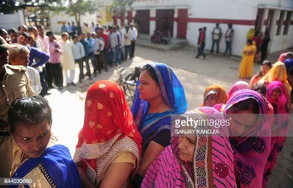 Indian women wait in a queue for their turn to vote at a polling station in the Naini area on the outskirts of Allahabad during the fourth phase of...