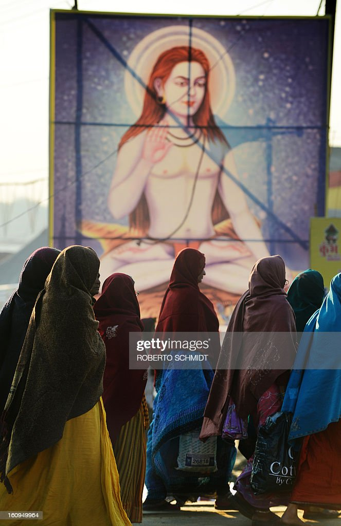 Indian women walk past a painting depicting a Hindu Guru on the grounds where the Kumbh Mela festival takes place in Allahabad on February 8, 2013. The Kumbh Mela in the town of Allahabad will see up to 100 million worshippers gather over 55 days to take a ritual bath in the holy waters, believed to cleanse sins and bestow blessings.