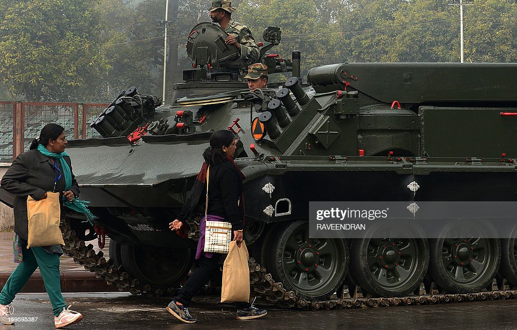 Indian women walk past a tank during a rehearsal for the Indian Republic Day parade in New Delhi on January 17, 2013. India will celebrate its 64th Republic Day on January 26 with a large military parade.