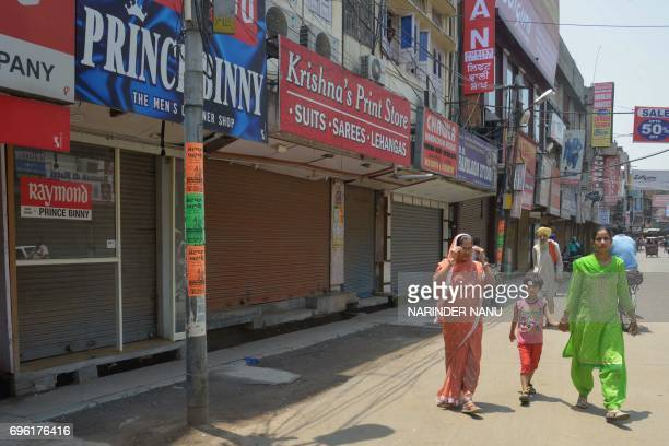 Indian women walk past clothes market stores closed during a protest against the central government's move to levy a goods and services tax on...