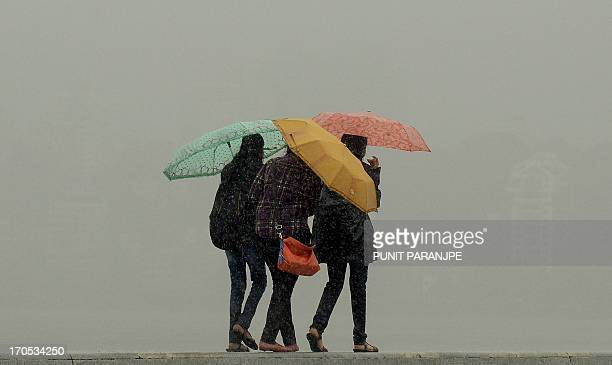 Indian women walk with umbrellas along the sea front during rain showers in Mumbai on June 14 2013 The weather department has forecast India will...