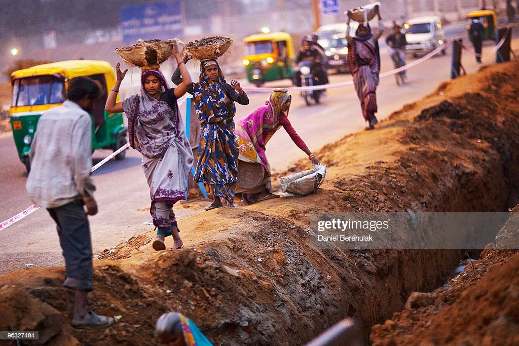 Indian women work at a construction project in front of the Jawaharlal Nehru Stadium on February 01, 2010 in New Delhi, India. The Commonwealth Games are due to be held in the Indian capital from October 3-14, 2010, but concerns remain over construction of its sporting and transport infrastructure. The sheer scale of the project has drawn an enormous population of migrant workers from all over India. This week the High Court of Delhi has sought a response from the Government over the alleged failure to provide all the benefits of labour laws to workers involved in construction work for the coming Commonwealth Games. Workers are being paid below the minimum wage in order to complete these projects whilst also being forced to live and work under sub standard conditions.