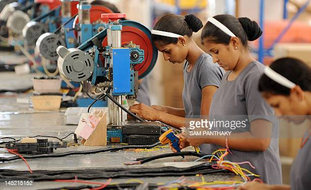Indian women work at the electrical wiring section of the OREVA E Bike manufacturing facility near Samakhiali of Kutch district some 240 kms from...