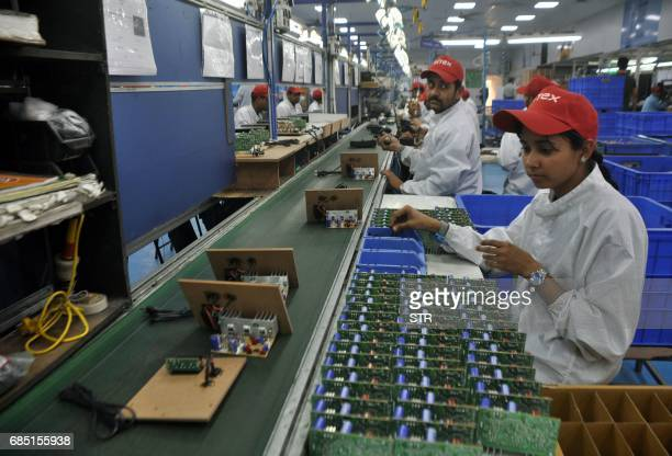 Indian workers assemble speakers at a factory in the business district of Bari Brahmana in Samba District on the outskirts of Jammu on May 19 2017...