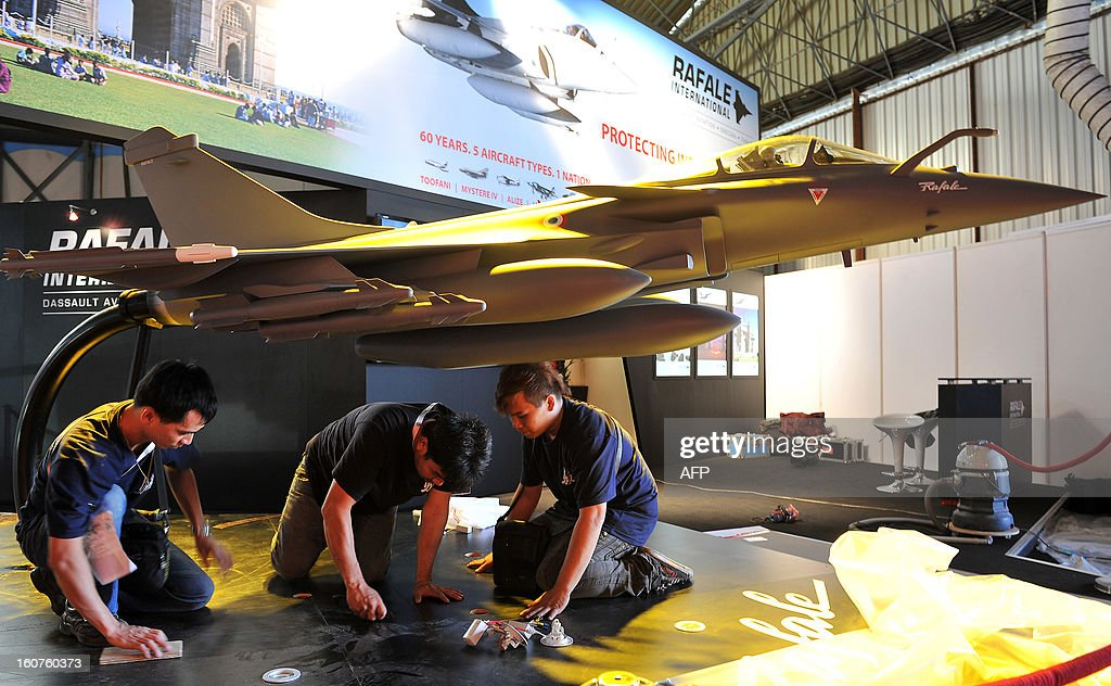 Indian workers at a Rafale fighter jet stall prepare an aircraft model ahead of the 9th edition of Aero India 2013 at the Yelahanka Air Force station in Bangalore on February 5, 2013. The 5-day event starting from January 6 will be inaugurated by Indian defence minister AK Antony and is a major platform for foreign vendors. The biennial event is crucial to international participants and investors at a time when the Indian government is set to spend USD 100 billion in the defence sector within the next five years. AFP PHOTO/Manjunath KIRAN