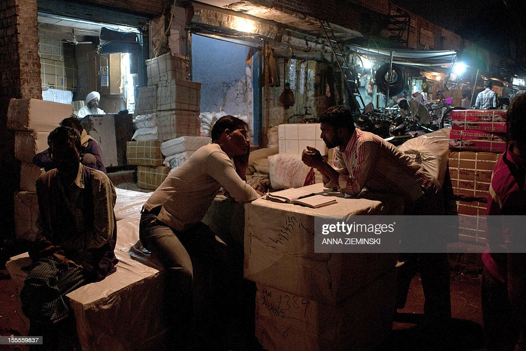 Indian workers chat as the proprietor of a parcel service sits in his shop in New Delhi on November 5, 2012. The ruling Congress party has rolled out its big guns to defend the move to let the likes of Walmart set up shop in India, but they are confronting an alliance stretching across the political spectrum. Prime Minister Manmohan Singh's left-leaning government announced in September that it was lowering the bar for foreign firms to operate in sectors ranging from retail to insurance, in a bid to revive its fortunes before elections in 2014 but elsewhere in the country, a broad array of Congress opponents are vowing to scupper the changes. AFP PHOTO/Anna ZIEMINSKI