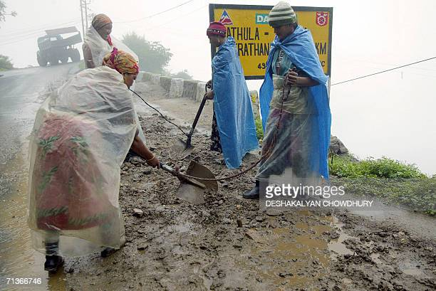 Indian workers clear mud from the road leading to the Nathu La Pass after a spell of rain 04 July 2006 Indian businessmen and local people expect a...