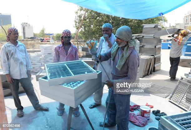 Indian workers colour parts of water coolers at a market in New Delhi on April 20 as demand for cooling equipment surges at the start of the summer...