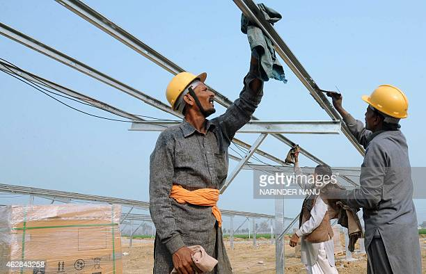 Indian workers construct part of the FranceIndia Solar Direct Punjab Solar Park project in Muradwala some 30kms from Fazilka on February 6 2015 The...