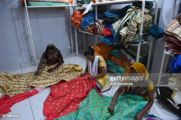 Indian workers do thread cutting on cloth at a stitiching and embroidery workshop impacted by a cloth shortage due to protests over the recently...
