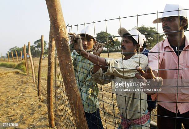 Indian workers erect fencing encircling the plot to be handed over to Indian carmaker Tata Motors at the village of Singur some 50 kms north of...