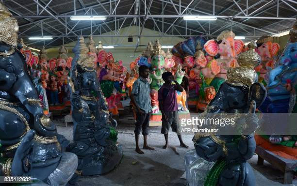 Indian workers gestures standing amongst finished idols of the elephantheaded Hindu deity Ganesha to a customer at a workshop ahead of the Ganesh...