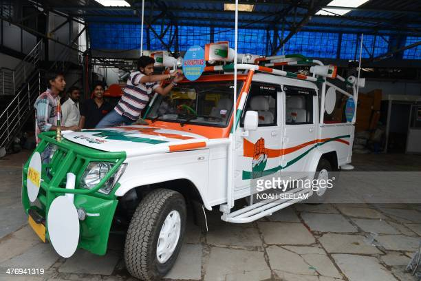 Indian workers give the final touches to an election campaign vehicle bearing Congress Party symbols and logos in Hyderabad on March 6 ahead of the...