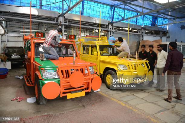 Indian workers give the final touches to election campaign vehicles bearing Bharatiya Janata Party and Telugu Desam party symbols and logos in...