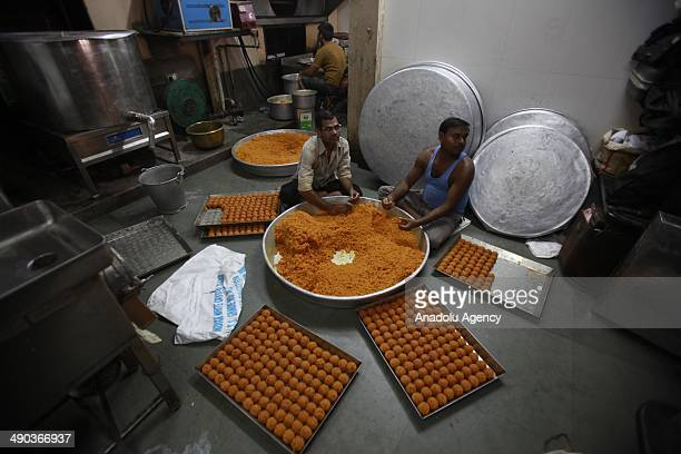 Indian workers make desserts within the organization of Bharatiya Janata Party for upcoming the 16th Lok Sabha constitute in Mumbai India on 14 May...