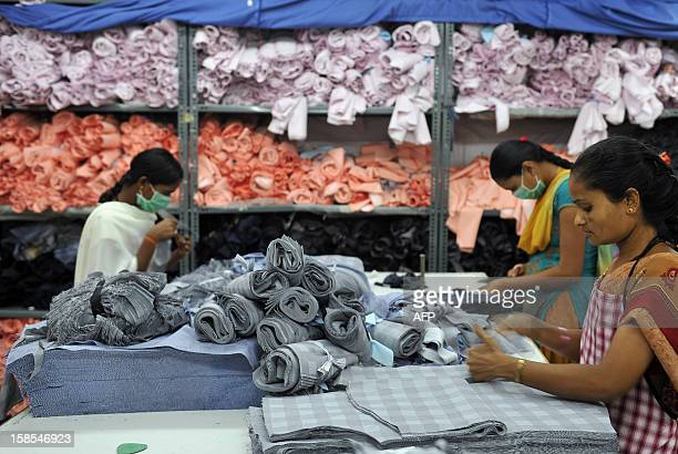 Indian workers of a private garment factory sort cut cloth material prior to stitching garments in Bangalore on November 21 2012 Garment workers'...