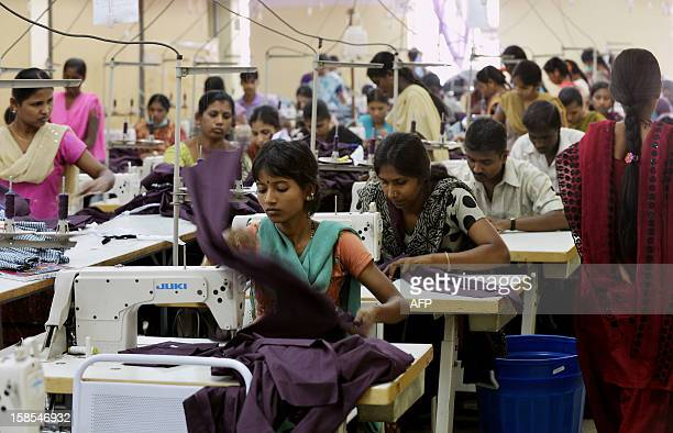 Indian workers of a private garment factory use machines while stitching apparel in Bangalore on November 21 2012 Garment workers' unions and human...