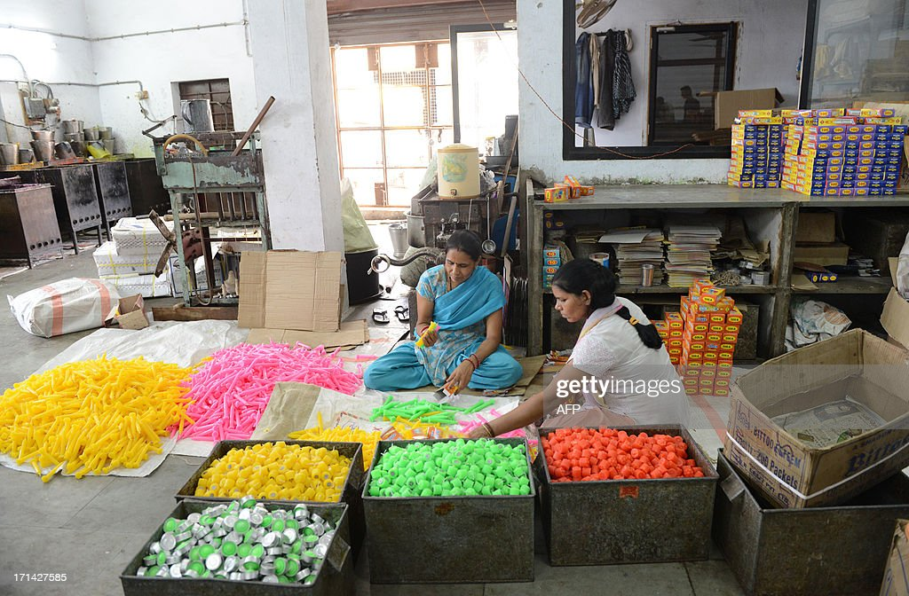 Indian workers pack wax candles at a factory in Ahmedabad on June 24, 2013. Wax candles are in great demand during the monsoon season when electricity blackouts are more common because of heavy rain. AFP PHOTO / Sam PANTHAKY