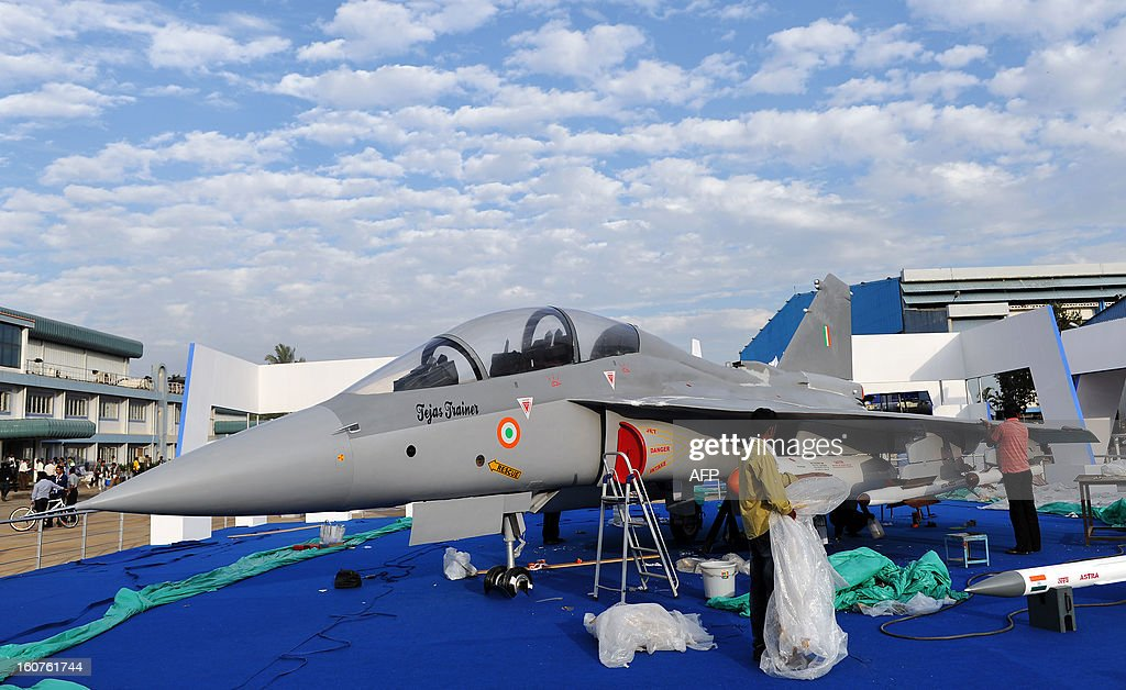 Indian workers prepare an Indian Air Force Tejas jet on display for the 9th edition of Aero India 2013 at the Yelahanka Air Force station in Bangalore on February 5, 2013