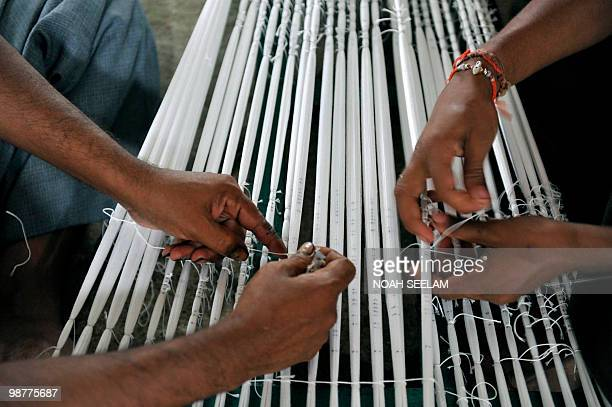 Indian workers prepare threads before weaving a saree on a hand loom in a workshop at Bhoodan Pochampally in Nalgonda District some 55 kms from...