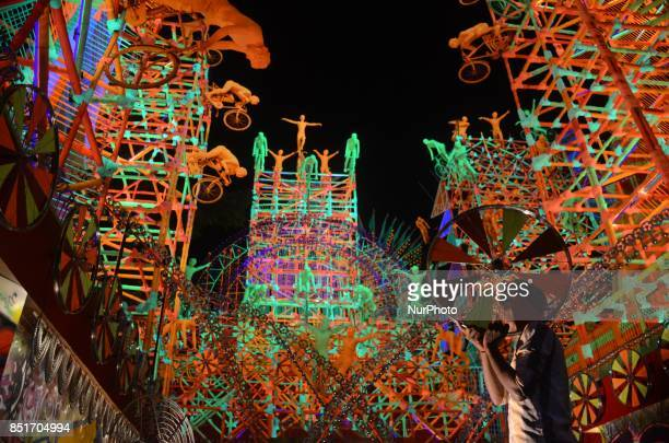 Indian workers prepares with cycle in the Puja pandal or a temporary platforms of goddess Durga ahead of Durga Puja festival in Kolkata India on...