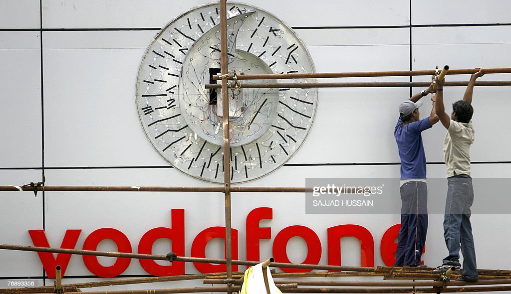 Indian workers put up the signboard of telecom firm 'Vodafone' at their corporate office in India's financial capital Mumbai 20 September 2007...