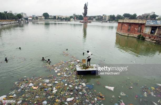 Indian workers remove plastic bags and other debris left by Hindu's marking the festival of Ganesh Chaturthi from Sur Sagar Lake in Vadodara on...