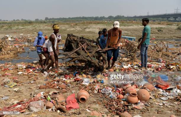 Indian workers remove religious offerings and frames of the idol of goddess Durga which were immersed in the Yamuna river after the Durga Puja...