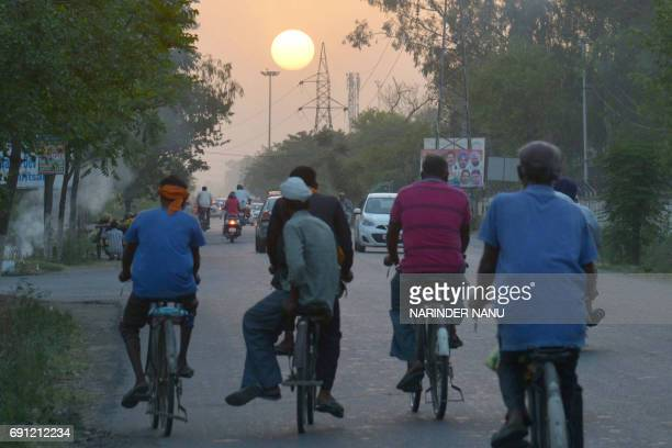 Indian workers return home on their bicycle during the sunset at outskirts of Amritsar on June 12017 / AFP PHOTO / NARINDER NANU
