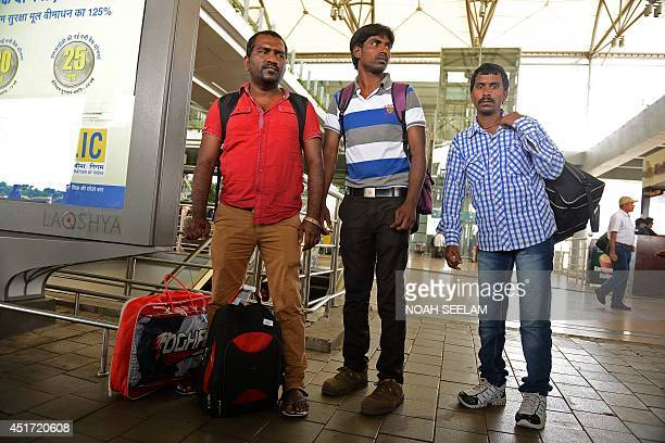 Indian workers returned from Iraq wait for transport after their arrival at Rajiv Gandhi International Airport in Hyderabad on July 5 2014 A group of...