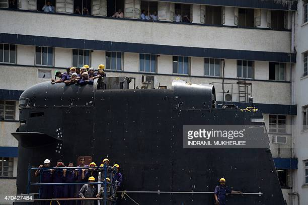 Indian workers stand on the bridge tower of a submarine as they watch the launch of INS Visakhapatnam the first Indian Navy P15B stealth destroyer is...